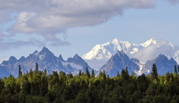 Snowy Alaskan mountains with evergreen trees in the forefront.