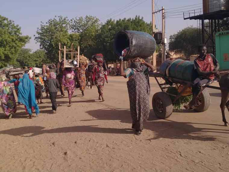 Families fleeing the violence in Western Darfur. A woman carries a barrel over her head next to a man with cart. Behind them are a multitude of families carrying their possessions.